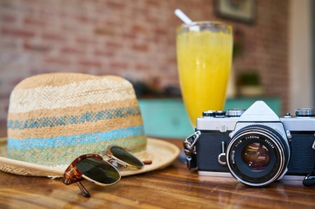 camera, sunglasses, hat, drink, table