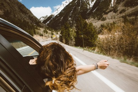 girl sticking head out window on road